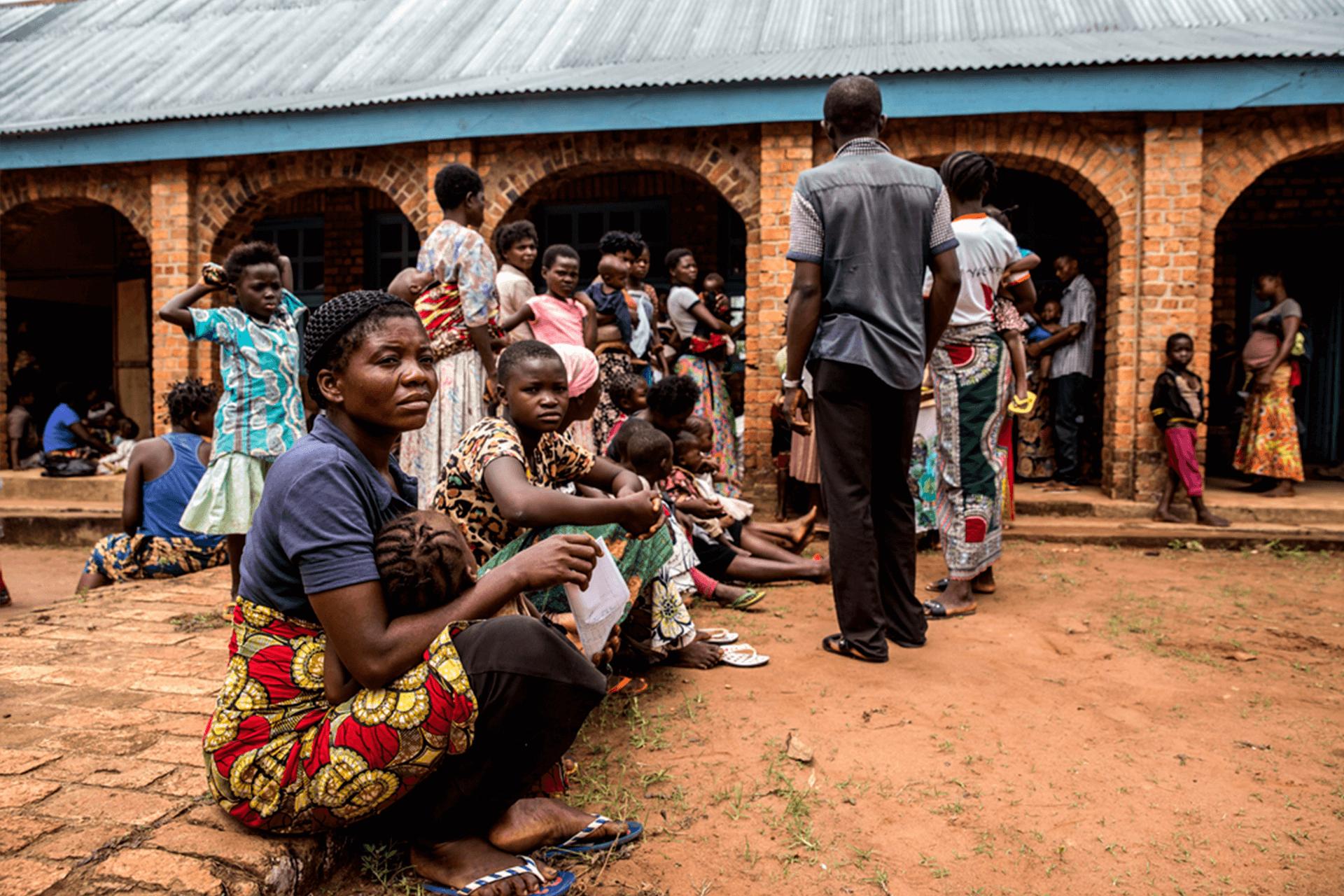 Mães e crianças que esperam na frente do centro de saúde de Mayi Munene para serem tratadas por desnutrição.
